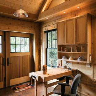 Immagine di un piccolo atelier country con pareti marroni, parquet scuro, nessun camino, scrivania autoportante e pavimento marrone
