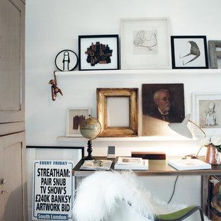 Eklektisk inredning av ett litet arbetsrum, med vita väggar och ett fristående skrivbord