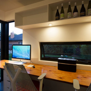 Свежая идея для дизайна: маленькая домашняя мастерская в современном стиле с белыми стенами, полом из ламината, серым полом и отдельно стоящим рабочим столом без камина - отличное фото интерьера