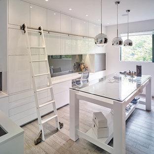 Bild på ett funkis hobbyrum, med vita väggar, ljust trägolv och ett inbyggt skrivbord