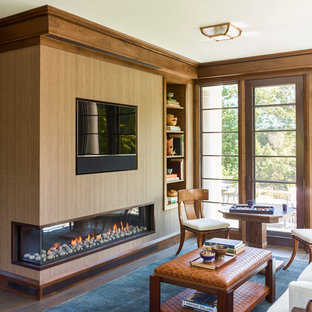 This is an example of a large traditional study in Boston with brown walls, dark hardwood flooring, a corner fireplace, a metal fireplace surround, a freestanding desk and brown floors.