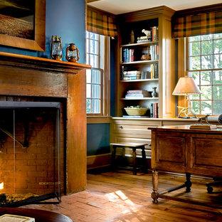 Idéer för ett klassiskt arbetsrum, med blå väggar, mellanmörkt trägolv, en spiselkrans i tegelsten, en standard öppen spis och brunt golv