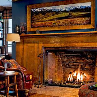 ニューヨークのトラディショナルスタイルのおしゃれなホームオフィス・書斎 (青い壁、無垢フローリング、レンガの暖炉まわり、標準型暖炉) の写真