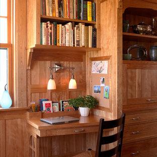 Exempel på ett amerikanskt arbetsrum, med ett inbyggt skrivbord, mellanmörkt trägolv och beige väggar