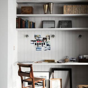 Inredning av ett industriellt litet hemmabibliotek, med ett inbyggt skrivbord, grå väggar och mörkt trägolv