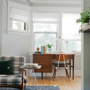 Home office - transitional freestanding desk medium tone wood floor home office idea in Minneapolis with gray walls