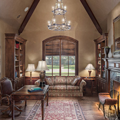 Example of a large classic freestanding desk dark wood floor study room design in Dallas with beige walls, a standard fireplace and a stone fireplace