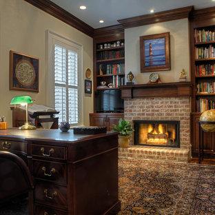 チャールストンのトラディショナルスタイルのおしゃれなホームオフィス・書斎 (レンガの暖炉まわり、標準型暖炉、無垢フローリング、自立型机、ライブラリー) の写真