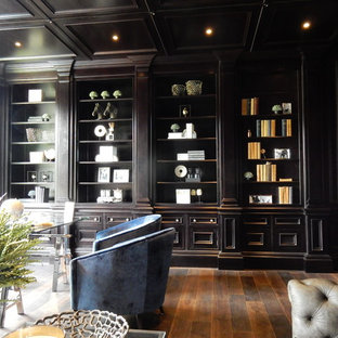 Inspiration for a large classic study in Surrey with black walls, dark hardwood flooring, a standard fireplace, a stone fireplace surround, a freestanding desk and brown floors.
