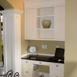 Inspiration för små moderna hemmabibliotek, med beige väggar, travertin golv och ett inbyggt skrivbord
