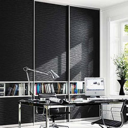 """Raumplus - """"Wave Black"""" - Crowded shelves of trade books and magazines may seem like clutter to some but in this working environment, those bits of literature are vital to the function of the space. Keep necessary material within site and hide the rest with this unique strip of clear glass surrounded with a deep """"Wave Black"""" texture. This multi-panel system reaches floor to ceiling thanks to Raumplus panel design which uses sections of alternating materials to permit panels to be taller and wider."""