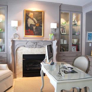 Klassisk inredning av ett stort hemmabibliotek, med heltäckningsmatta, en standard öppen spis, en spiselkrans i sten, ett fristående skrivbord och rosa väggar