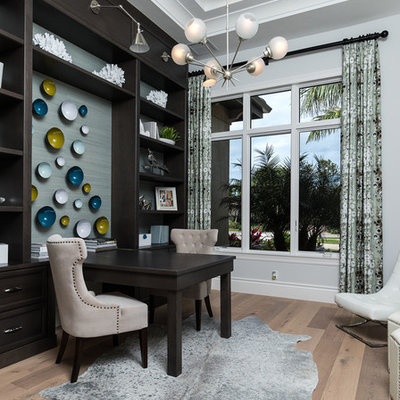 Example of a mid-sized tuscan built-in desk light wood floor and beige floor study room design in Other with gray walls and no fireplace