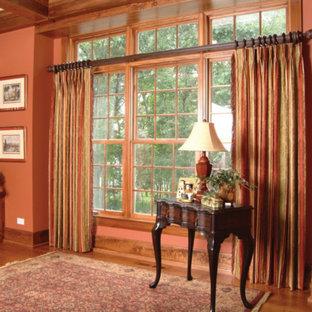 Ejemplo de despacho tradicional, de tamaño medio, sin chimenea, con paredes rosas, suelo de madera oscura, escritorio independiente y suelo marrón