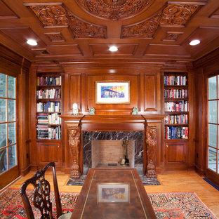 Imagen de estudio tradicional, extra grande, con escritorio empotrado, paredes amarillas, suelo laminado, chimenea tradicional, marco de chimenea de piedra y suelo amarillo
