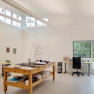 Large farmhouse built-in desk concrete floor home studio photo in Boston with white walls