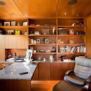 Cette image montre un bureau design de taille moyenne avec un mur marron, un sol en bois brun, une cheminée ribbon et un bureau intégré.