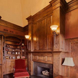 Foto di un ufficio classico di medie dimensioni con pareti gialle, parquet scuro, camino classico, scrivania autoportante e cornice del camino in pietra