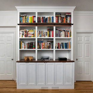 Idee per uno studio chic di medie dimensioni con libreria, pareti bianche, parquet chiaro, scrivania incassata e pavimento giallo
