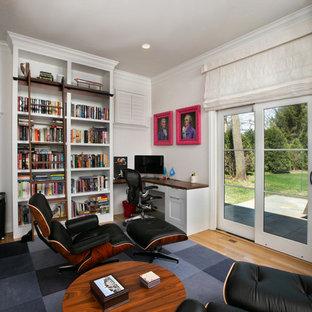 Immagine di uno studio classico di medie dimensioni con libreria, pareti bianche, parquet chiaro, scrivania incassata e pavimento giallo