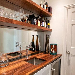 Modelo de despacho clásico, de tamaño medio, con paredes blancas, suelo de madera clara, escritorio empotrado y suelo amarillo