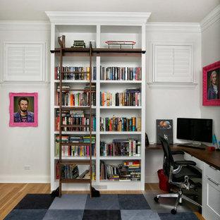 Inredning av ett klassiskt mellanstort arbetsrum, med ett bibliotek, vita väggar, ljust trägolv, ett inbyggt skrivbord och gult golv
