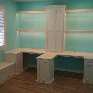 Ispirazione per un grande ufficio chic con pareti verdi, pavimento in laminato, scrivania incassata e pavimento marrone