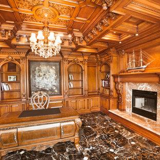 ニューヨークの中サイズのトラディショナルスタイルのおしゃれな書斎 (茶色い壁、大理石の床、標準型暖炉、石材の暖炉まわり、自立型机) の写真