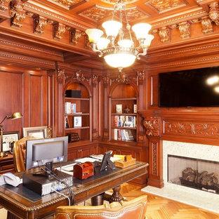 Inspiration för mellanstora klassiska hemmabibliotek, med bruna väggar, mellanmörkt trägolv, en standard öppen spis, en spiselkrans i sten och ett fristående skrivbord