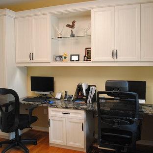 Ispirazione per un ufficio boho chic con pareti gialle, pavimento in legno massello medio e scrivania incassata