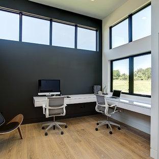 グランドラピッズの中サイズのコンテンポラリースタイルのおしゃれな書斎 (黒い壁、淡色無垢フローリング、造り付け机、暖炉なし、ベージュの床) の写真