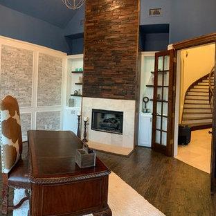 ダラスの広いカントリー風おしゃれな書斎 (白い壁、標準型暖炉、木材の暖炉まわり、自立型机、茶色い床) の写真