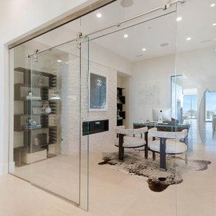 オレンジカウンティの中くらいのコンテンポラリースタイルのおしゃれなホームオフィス・書斎 (ライブラリー、白い壁、セラミックタイルの床、標準型暖炉、石材の暖炉まわり、自立型机、ベージュの床) の写真