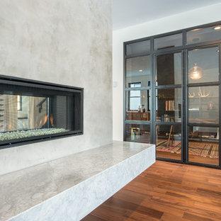 Cette image montre un bureau design avec un mur noir, un sol en bois brun, une cheminée double-face, un manteau de cheminée en béton et un bureau indépendant.