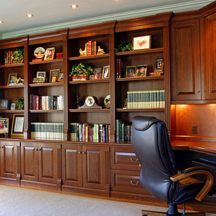 Idéer för att renovera ett stort vintage hemmabibliotek, med beige väggar, ljust trägolv och ett inbyggt skrivbord