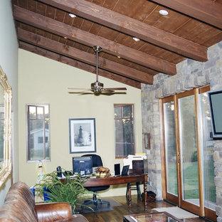 Esempio di un ufficio mediterraneo con pareti gialle, pavimento in legno massello medio, scrivania autoportante e nessun camino