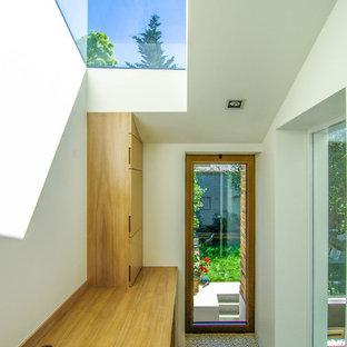 Foto di un piccolo ufficio moderno con pareti bianche, pavimento con piastrelle in ceramica e scrivania incassata