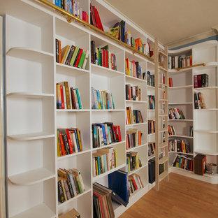 ロンドンの広いコンテンポラリースタイルのおしゃれなホームオフィス・書斎 (青い壁、茶色い床、ライブラリー、ラミネートの床) の写真