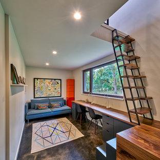 グランドラピッズのコンテンポラリースタイルのおしゃれなホームオフィス・書斎 (グレーの壁、コンクリートの床、造り付け机、グレーの床) の写真