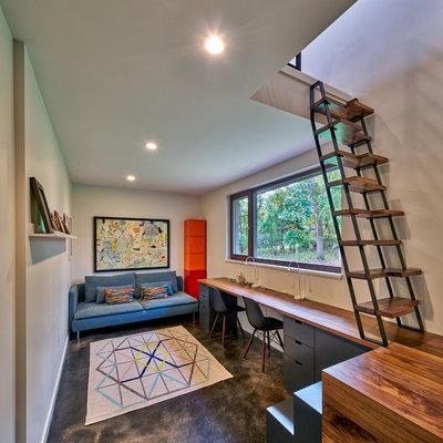Trendy built-in desk concrete floor and gray floor home office photo in Grand Rapids with gray walls