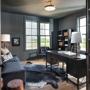 Réalisation d'un bureau champêtre avec un mur gris, un sol en bois brun, un bureau indépendant et un sol marron.