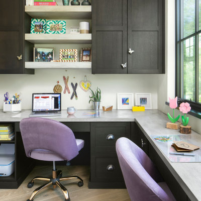 Home office - country built-in desk light wood floor and beige floor home office idea in Denver with white walls