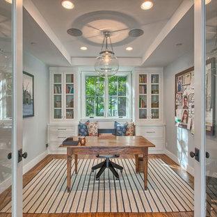 Imagen de despacho extra grande, sin chimenea, con paredes grises, suelo de madera clara y escritorio independiente
