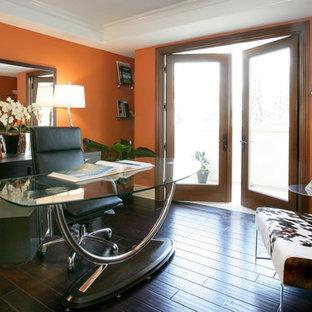 Imagen de despacho moderno, grande, sin chimenea, con parades naranjas, suelo de madera oscura y escritorio independiente