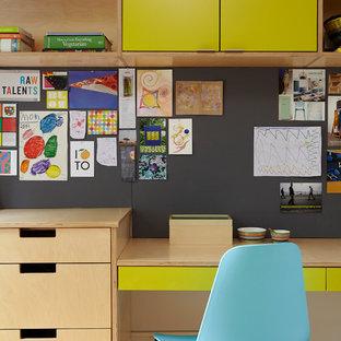 Cette image montre un bureau nordique de taille moyenne avec un bureau intégré, un mur blanc, un sol en bois clair, aucune cheminée et un sol beige.