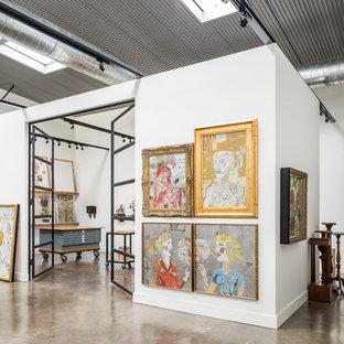 Ispirazione per un grande atelier industriale con pareti bianche e pavimento in cemento