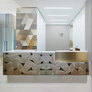 ロサンゼルスの中サイズのコンテンポラリースタイルのおしゃれなホームオフィス・書斎 (白い壁、暖炉なし、造り付け机、ベージュの床、ライムストーンの床) の写真