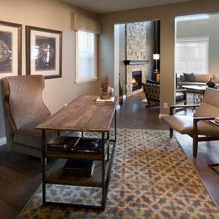 Foto di uno studio minimal con pareti grigie, pavimento in vinile, camino classico, cornice del camino in pietra e scrivania autoportante