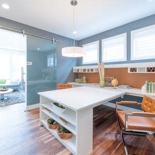 Exemple d'un bureau atelier tendance de taille moyenne avec un mur gris, un sol en bois brun, un bureau intégré et un sol marron.