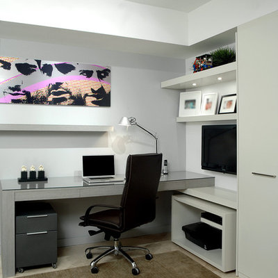 Example of a trendy built-in desk home office design in Miami with gray walls